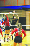 Photos by Greg Bird Caitlyn Strunk (middle) goes up for a block.